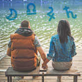 couple sitting on dock with astrology symbols around
