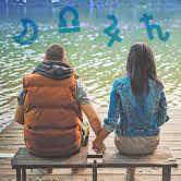 couple sitting on dock with astrology symbols around