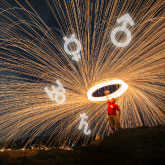 man in center of fireworks and zodiac symbols