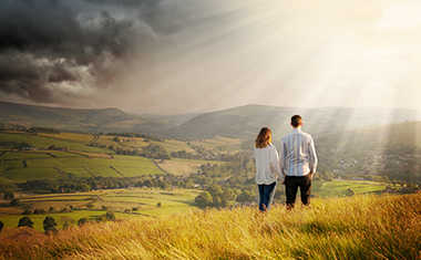 couple in sunny field looking at beautiful view