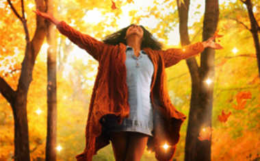 sunny fall day: happy woman with arms outstretched