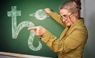 teacher with saturn on chalkboard